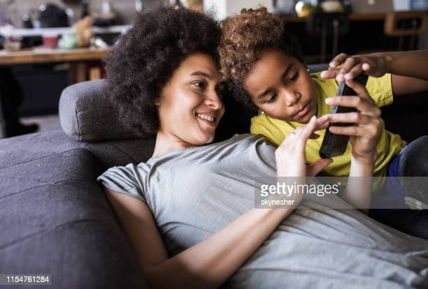african american mother and daughter using cell phone on sofa at home. - candid forum stock pictures, royalty-free photos & images