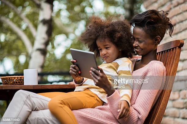 Afro-americana mãe e filha com tablet digital em terrace.