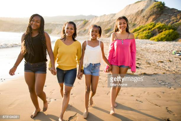 african american mother and daughters walking on beach - ragazzine scalze foto e immagini stock