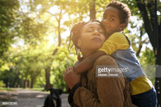 African American mother and her daughter enjoying in park together and hugging.