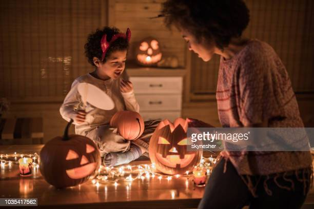 african american mother and her son preparing for halloween party at home. - halloween decoration stock pictures, royalty-free photos & images