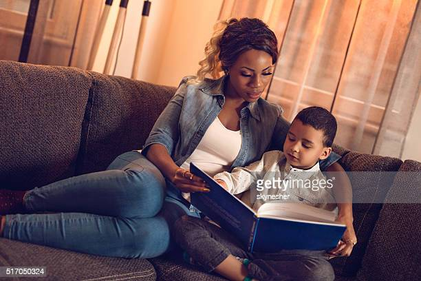 African American mother and son reading book at home.