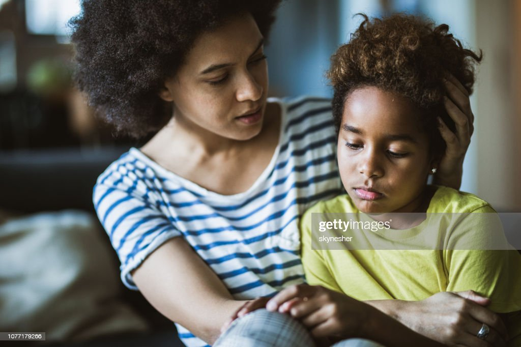 African American mother consoling her sad girl at home. : Stock Photo