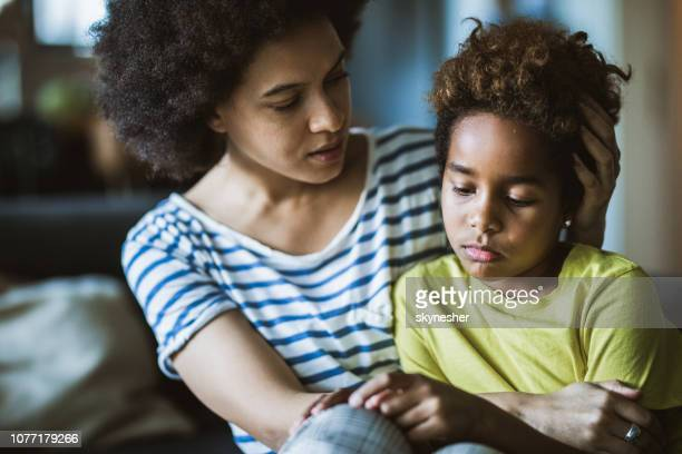 african american mother consoling her sad girl at home. - distraught stock pictures, royalty-free photos & images