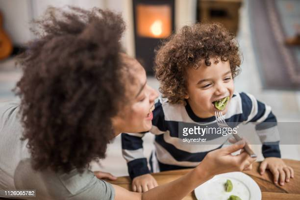 african american mother feeding her happy son with kiwi. - kiwi fruit stock pictures, royalty-free photos & images