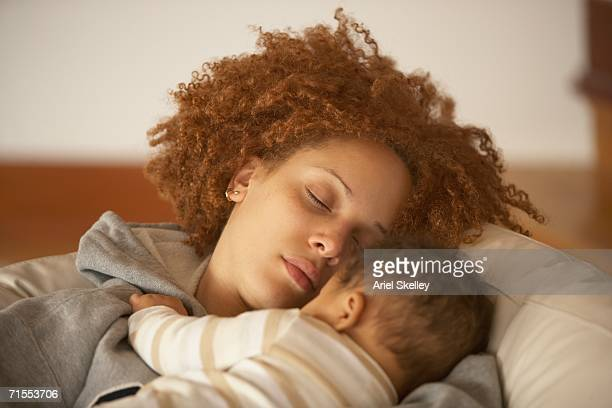 african american mother sleeping on sofa with baby - babyhood stock pictures, royalty-free photos & images