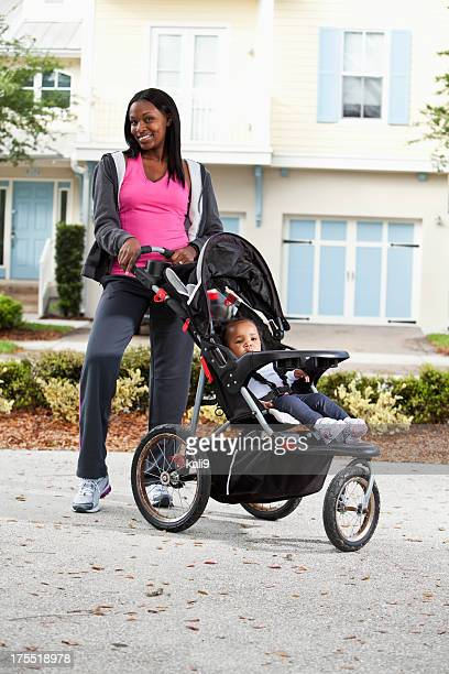 African American mother with baby in jogging stroller
