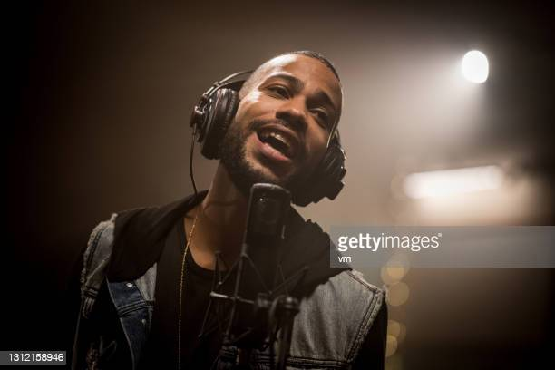 african american musician singing on professional microphone in recording studio. - singer stock pictures, royalty-free photos & images
