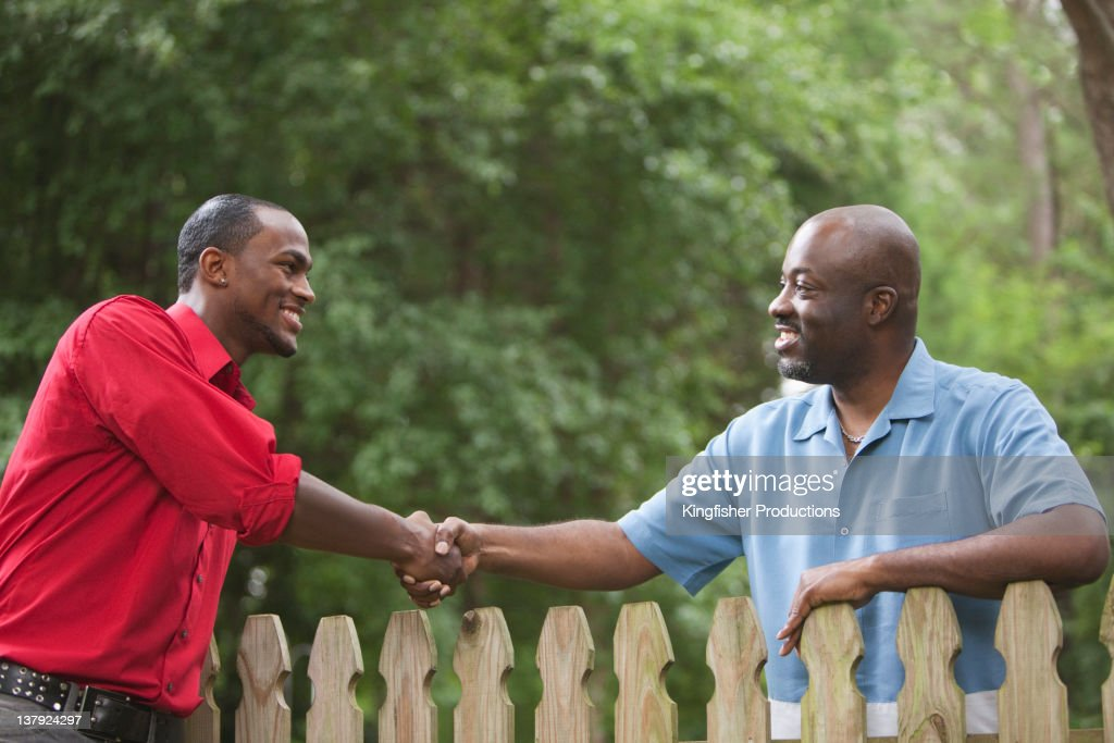 African American neighbors greeting each other over fence : Stock Photo