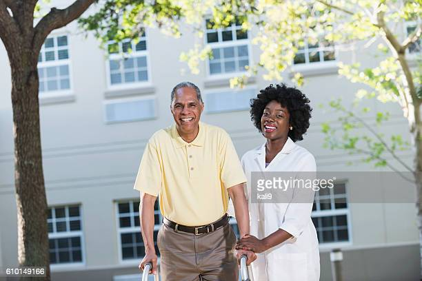 African American nurse assisting man with walker