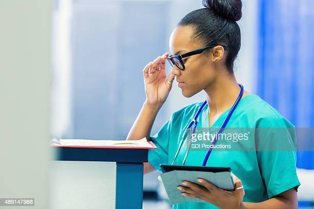 African American enfermera de comprobación registros de la paciente en el hospital