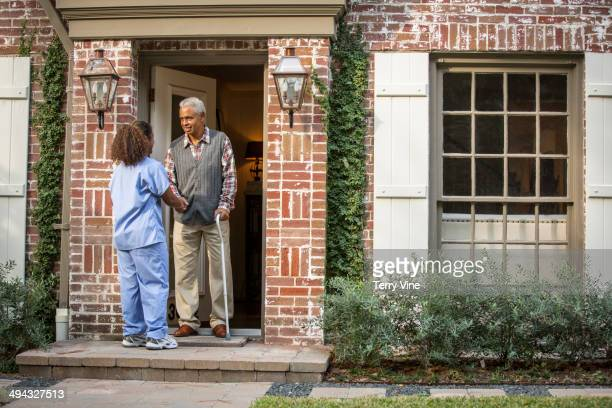 African American nurse helping patient use cane
