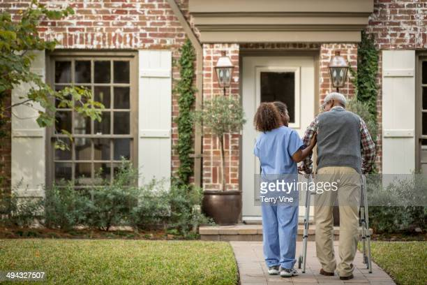 african american nurse helping patient use walker - patient safety stock pictures, royalty-free photos & images