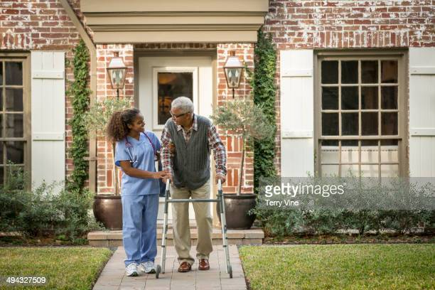 African American nurse helping patient use walker