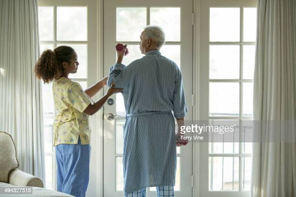 African American nurse helping patient with physical therapy