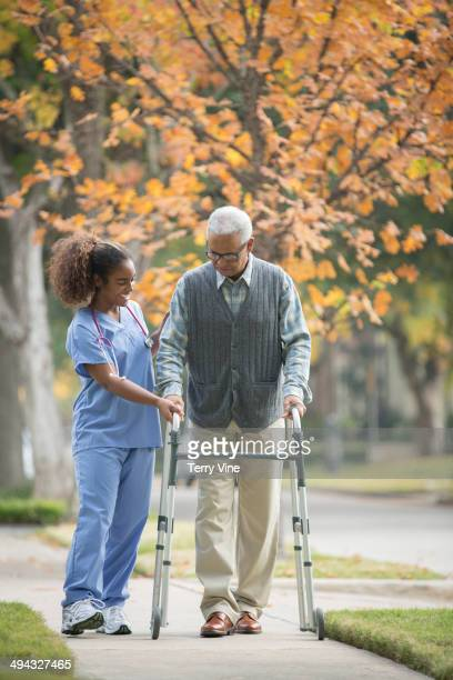 african american nurse helping senior patient use walker - african american man helping elderly stock pictures, royalty-free photos & images