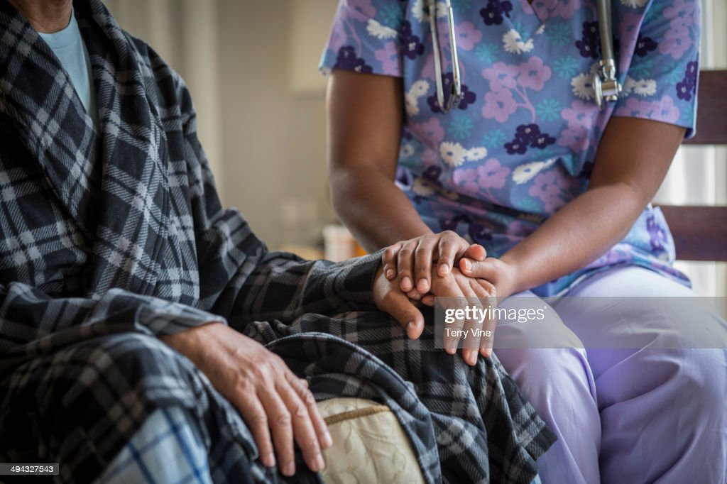 African American nurse holding patient's hand : Stock Photo