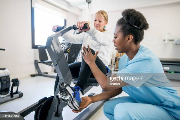 african american occupational therapist explaining a patient how to use the static bicycle - bounce back stock photos and pictures