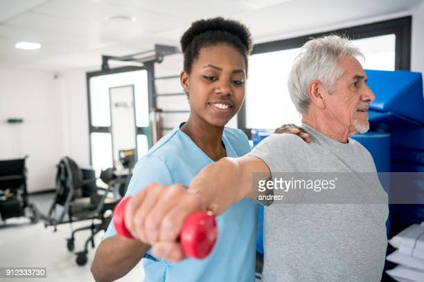 African american occupational therapist helping a senior patient with his shoulder workout