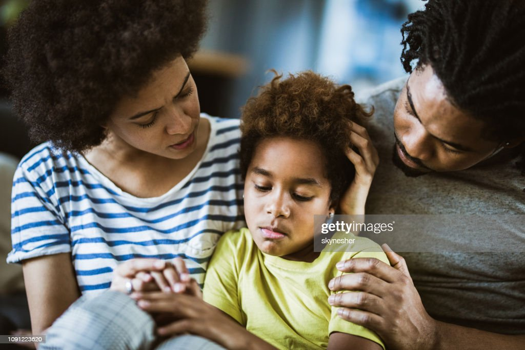 African American parents consoling their sad girl at home. : Stock Photo
