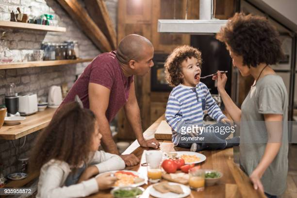 African American parents having breakfast with their kids in the kitchen.