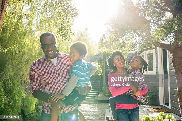 African American parents in garden carrying their children