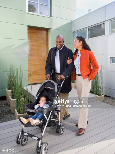 African American parents pushing baby in stroller