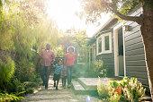 African American parents with two children walking in garden