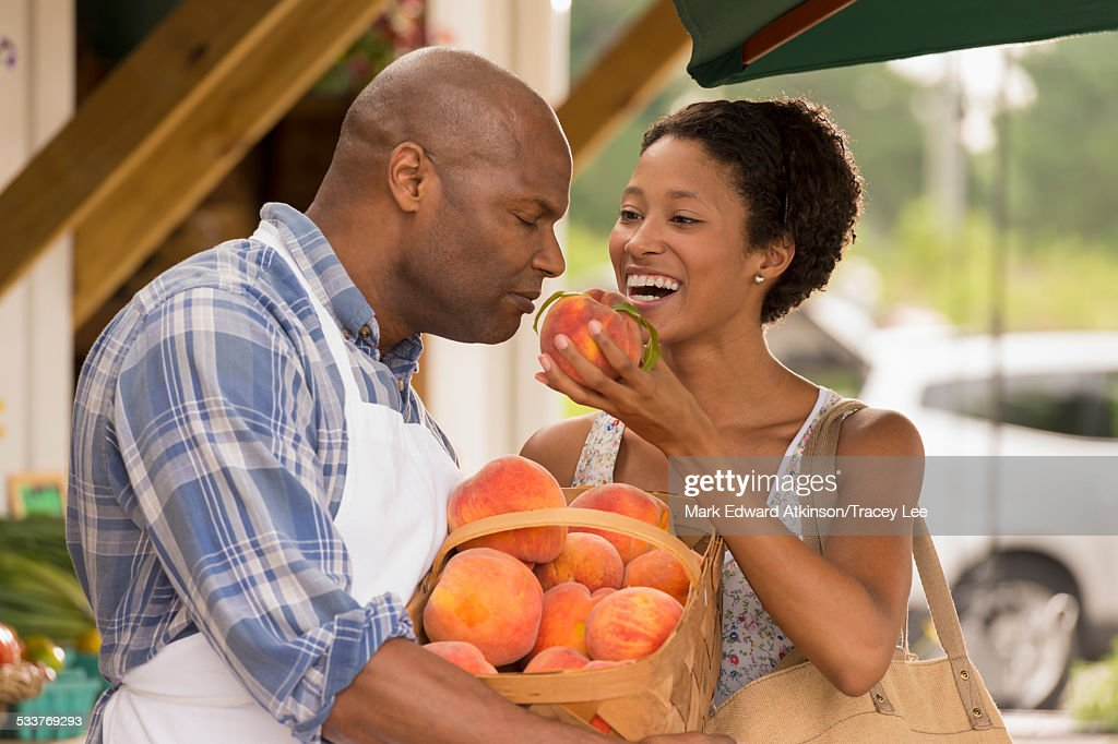 African American people smelling produce at farmers market : Foto stock