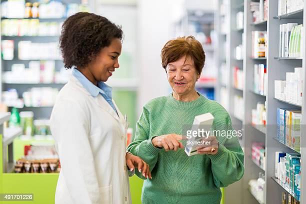 Afro-americano farmacêutico para uma mulher idosa a ajudar.