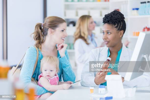 African American pharmacist consults with customer