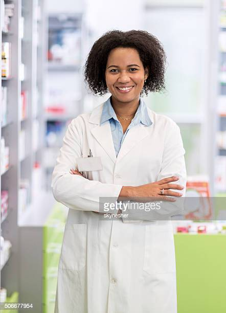 African American pharmacist with arms crossed in pharmacy.