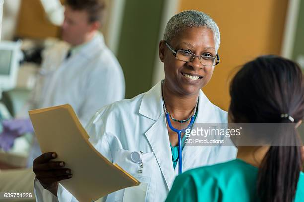 African American phlebotomist talks with nurse