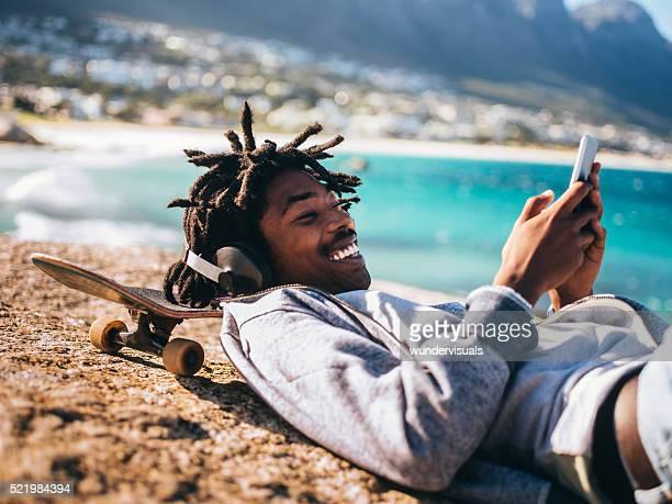 afro-américain au repos, de rire et regardant de smartphone - rasta photos et images de collection