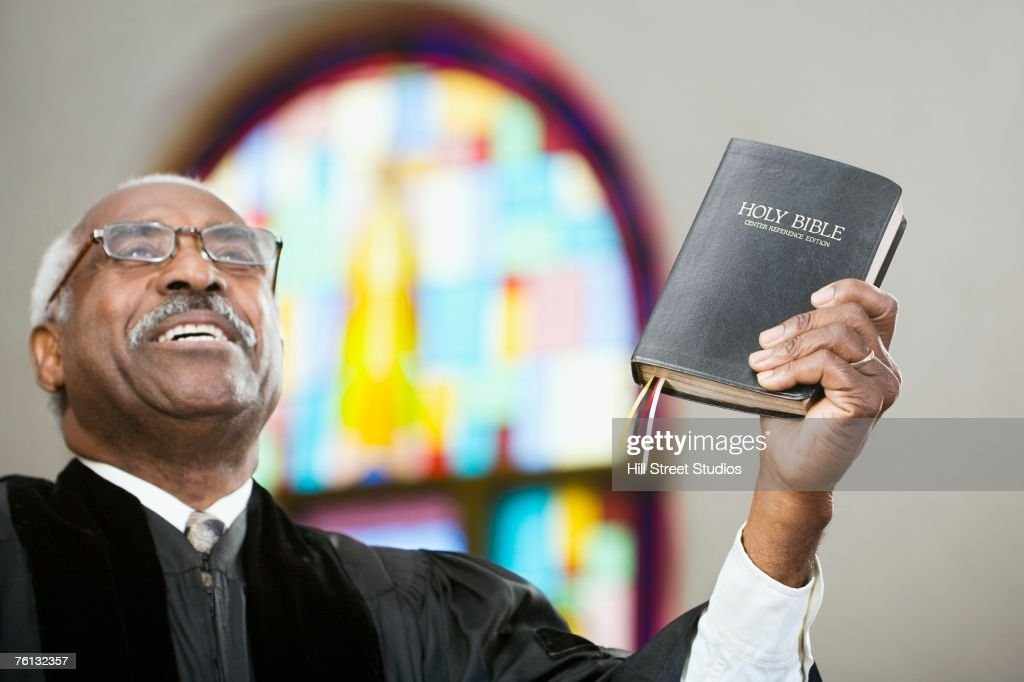 African American Reverend holding up Bible : Stock Photo