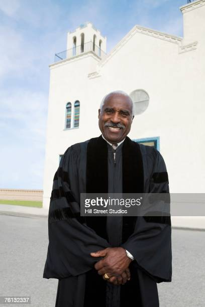 African American Reverend in front of church