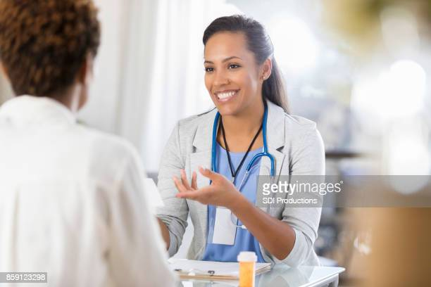 african american reviews prescription medication with patient - female doctor stock photos and pictures