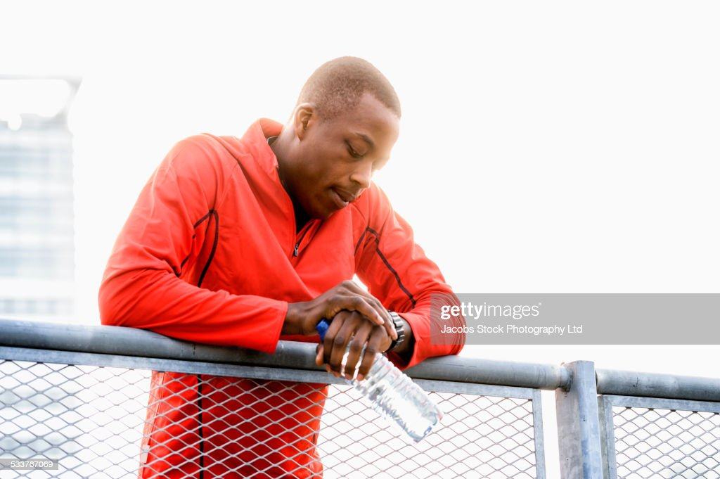 African American runner checking his watch on railing : Foto stock