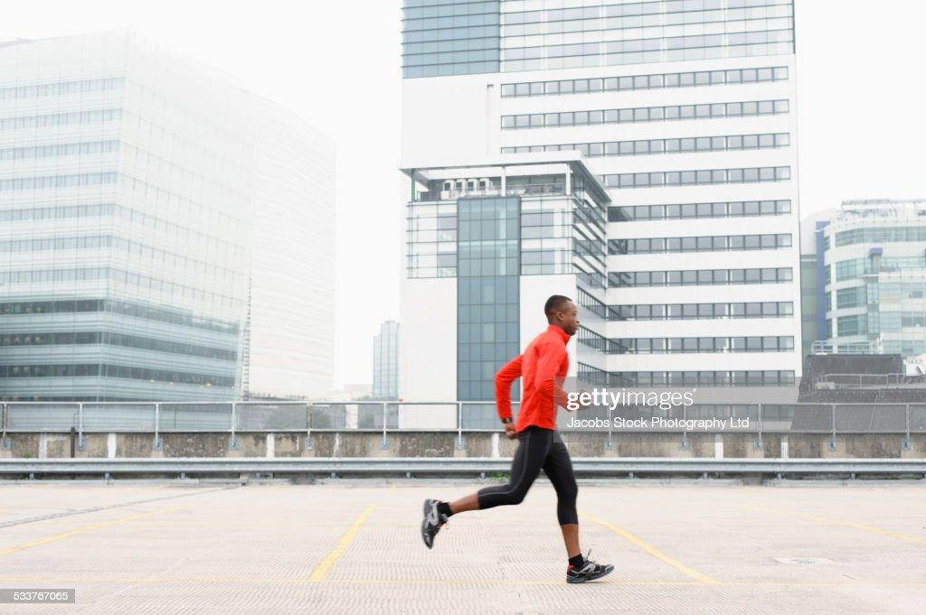 African American runner jogging in city : Foto stock