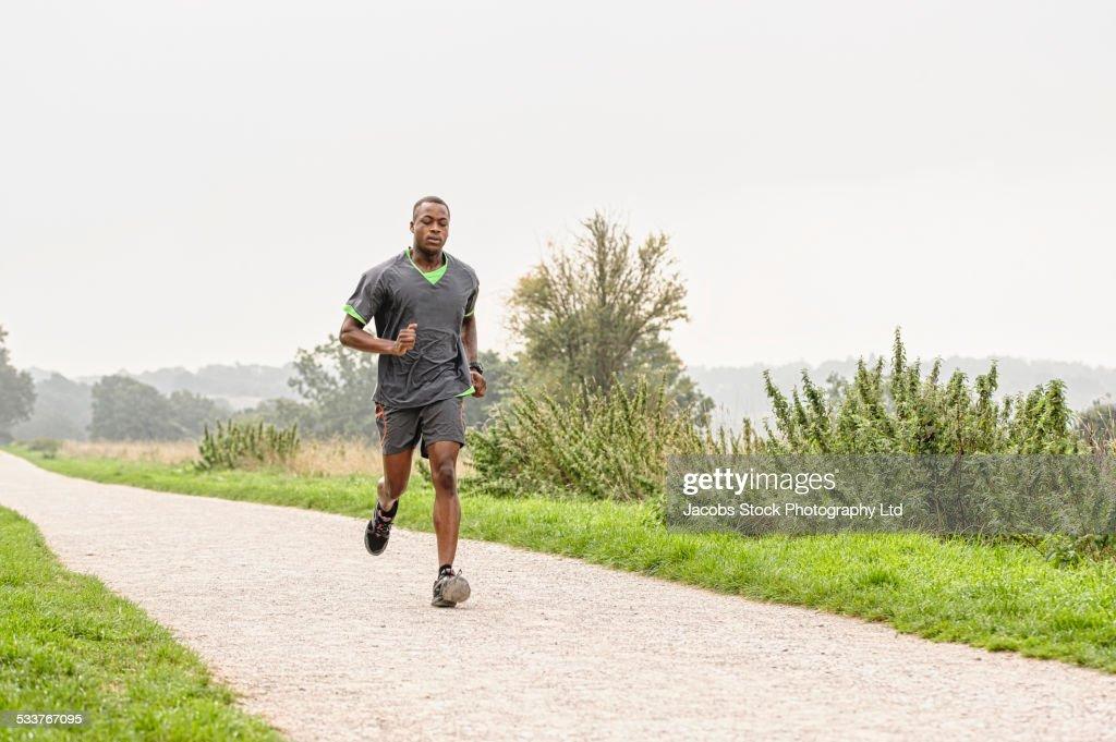 African American runner jogging on gravel path : Foto stock