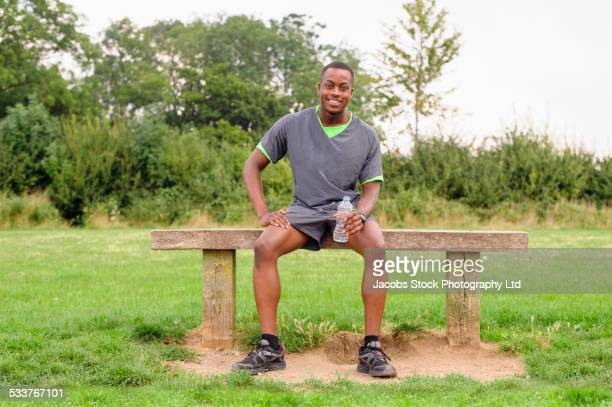 African American runner resting on park bench