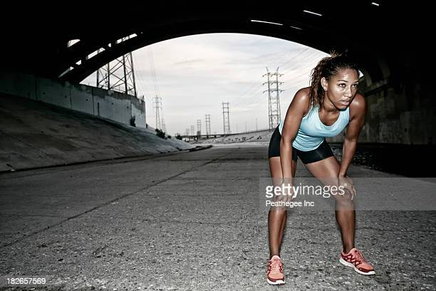 African American runner resting under overpass