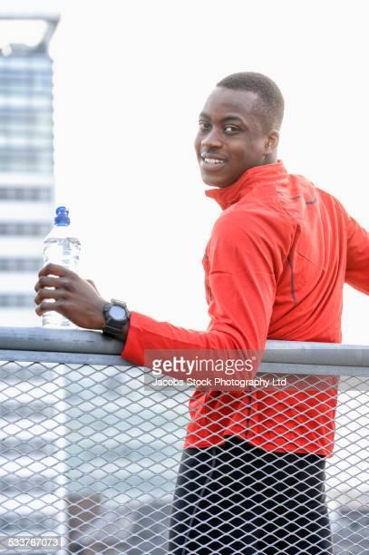African American runner smiling on railing