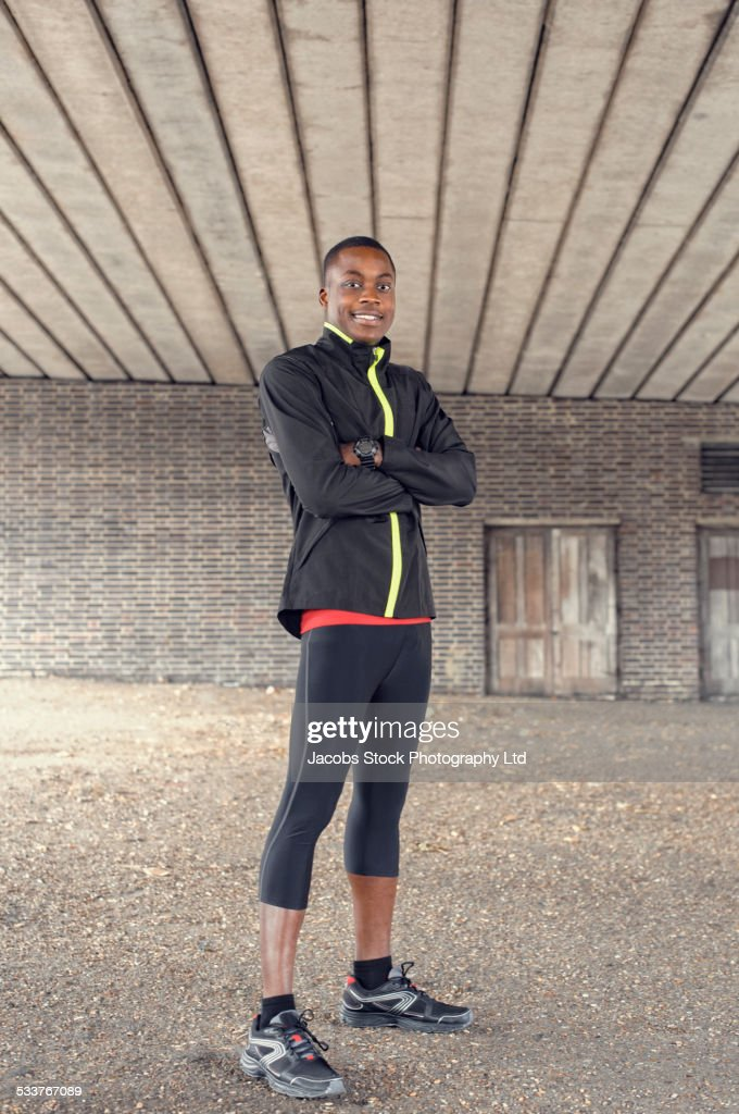 African American runner standing under concrete structure : Foto stock