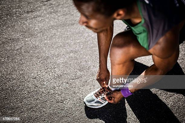 african american runner tying his laces and looking ahead - black shoe stock photos and pictures