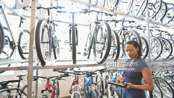 african american saleswoman using digital tablet in bicycle shop - bicycle shop stock pictures, royalty-free photos & images