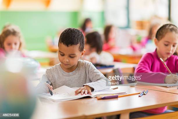 African American schoolboy drawing on a class at school.