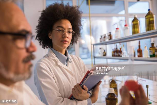 african american scientist cooperating with her male colleague in a laboratory. - bioquímico imagens e fotografias de stock
