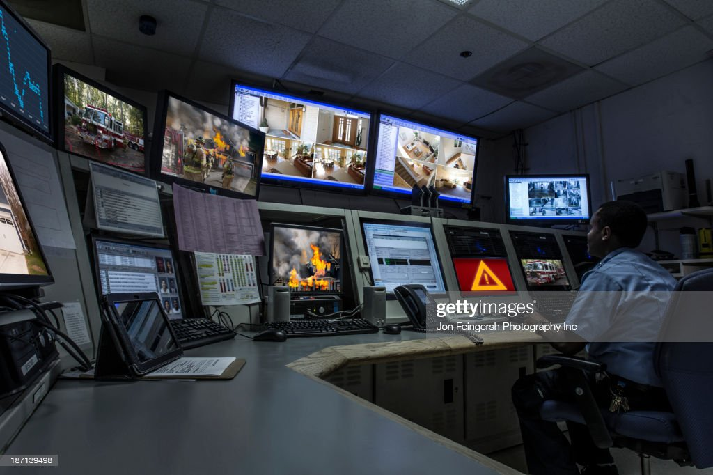 African American security officer working in control room : Stock Photo