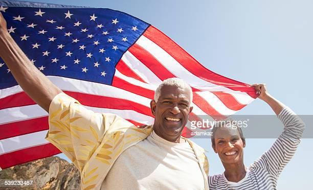 African American Senior Couple Carrying USA Flag